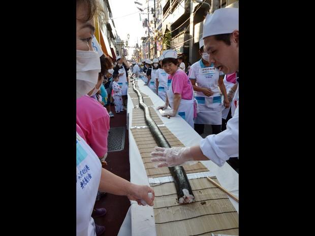 Um chef japonês prepara-se para começar a cortar um rolo de sushi com 120 metros de comprimento e servir para visitantes durante tradicional festival de verão em Tóquio. Centenas de crianças e voluntários participaram do evento. (Foto: Yoshikazu Tsuno/AFP)