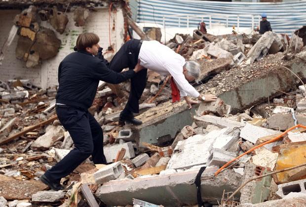 O presidente do Chile, Sebastian Piñera, tropeça e cai durante visita a escombros perto de Santiago (Foto: Sebastián Rodríguez/AFP)