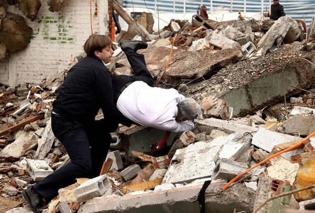 O prefeito de Puente Alto, German Codina, tenta socorrer o presidente do Chile, Sebastian Piñera, em uma queda durante visita a habitações demolidas perto de Santiago (Foto: Sebastián Rodríguez/AFP)