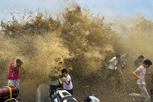 Grupo de chineses e turistas foi atingido por uma onda às margens do rio Qiantang (Foto: Reuters)