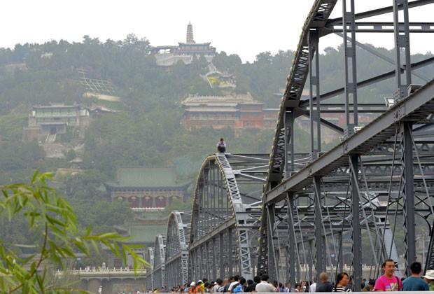 Homem tenta se jogar de ponte na China nesta quarta-feira (28) (Foto: China Daily/Reuters)