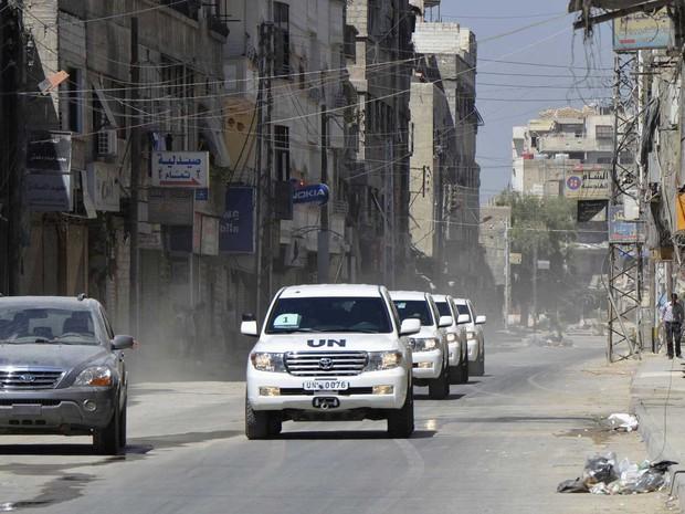 Veículos da ONU levam inspetores, sob escolta do Exército Livre da Síria, pela área de Ghouta que foi vítima de ataque na semana anterior (Foto: Bassam Khabieh/Reuters)