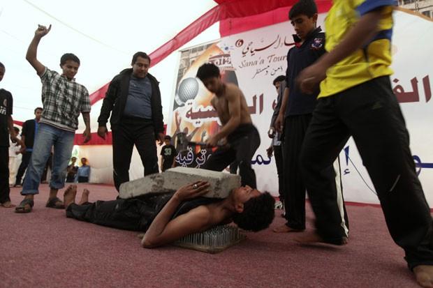 Artista de rua exibiu sua técnica ao deixar outro quebrar um bloco de concreto sobre seu peito (Foto: Mohamed al-Sayaghi/Reuters)