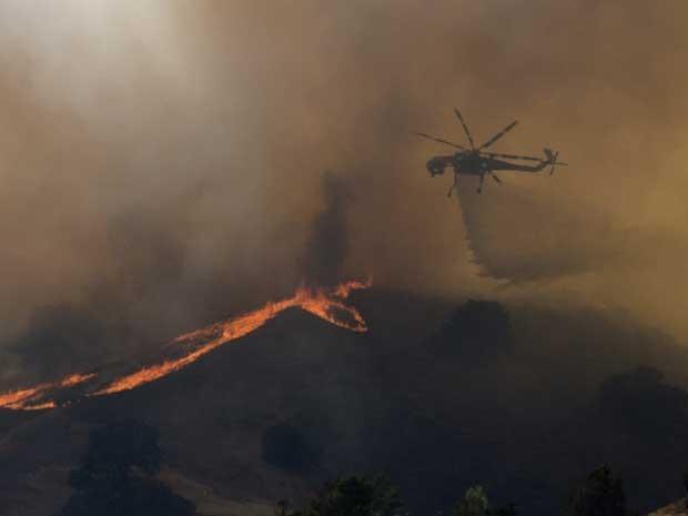 Helicóptero despeja água sobre incêndio na Califórnia. (Foto: Joe Klamar / AFP Photo)