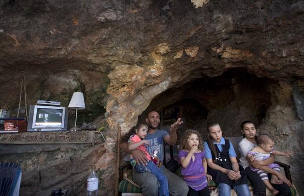 Khaled Zir al-Husseini e suas filhas na nova casa-caverna em Silwan, leste de Jerusalém (Foto: Ahmad Gharabli/AFP)