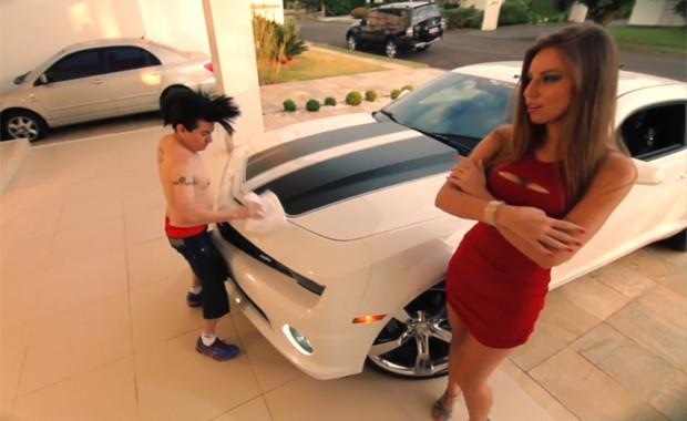 O cantor Solimões, ao fundo, limpa um Camaro em clipe de 'O cowboy vai te pegar', que brinca com temas de músicas sertanejas atuais (Foto: Divulgação)
