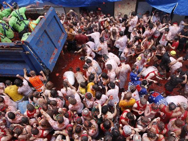 Multidão participa da Tomatina, guerra de tomates celebrada anualmente na vila de Buñol, na Espanha. A organização estima que 20 mil pessoas participam do evento, que passou a ser cobrado para quem não é morador da vila. O preço é 10 euros. (Foto: Alberto Saiz/AP)