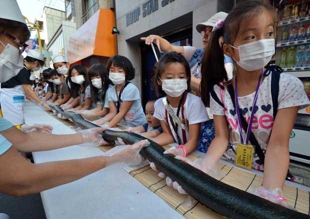 Crianças auxiliam na produção do sushi gigante durante um festival em Tóquio nesta terça-feira (27) (Foto: Yoshikazu Tsuno/ AFP)