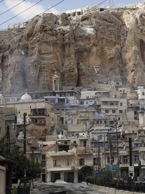 Foto tirada em 18 de setembro mostra vista geral da cidade cristã Maalula, durante conflito entre forças do governo e rebeldes. Convento fica entre colina controlada por rebeldes e praça dominada pelo exército. (Foto: AFP)