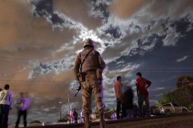 Policiais e moradores no local do ataque desta segunda-feira (23) próximo a Ciudade Juárez, no México (Foto: Reuters)