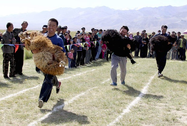 Participantes precisavam carregar suas ovelhas (Foto: Reuters/China Daily)