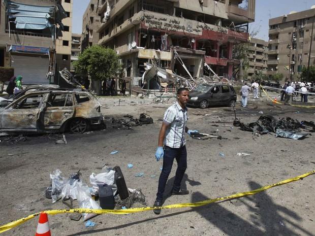 Policial à paisana inspeciona local de explosão perto da casa do ministro do Interior do Egito, Mohamed Ibrahim, em Nasr, no Cairo. O ministro sobreviveu ao atentado, que usou uma bomba acionada por controle remoto. (Foto: Amr Abdallah Dalsh/Reuters)