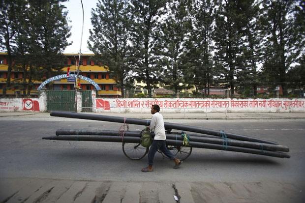 Um homem foi flagrado transportando canos enormes em sua bicicleta em Katmandu, no Nepal. Os canos tinham mais do triplo do tamanho da bicicleta (Foto: Navesh Chitrakar/Reuters)