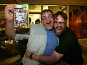 Empolgado, fã do game 'Grand Theft Auto 5' mostra o jogo recém-adquirido enquanto recebe um abraço do animador Michael Petterson (dir.) após a abertura das vendas à meia-noite em loja de Encinitas, Califórnia. Petterson trabalhou na animação de 'GTA 5'. (Foto: Mike Blake/Reuters)