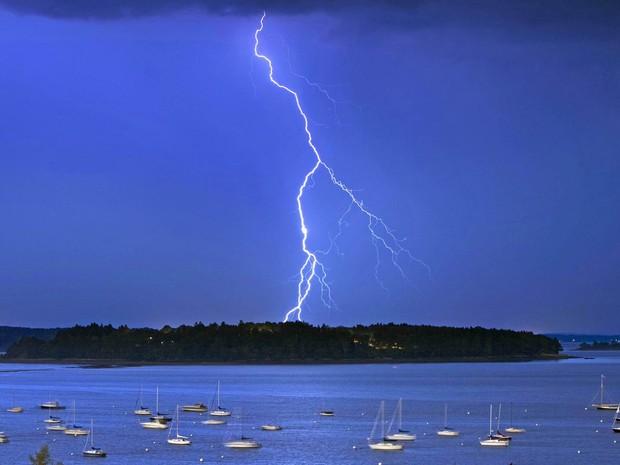 Raio corta céu ao norte da ilha de Macworth, em Portland, Maine. O Serviço Nacional de Meteorologia dos EUA informou que mais de mil raios por hora atingiram o solo no ápice da tempestade na quarta (11). A foto da véspera foi divulgada nesta quinta (12). (Foto: Robert F. Bukaty/AP)