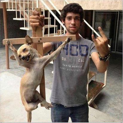 Rapaz aparece ao lado de um cãozinho preso em uma cruz! Verdade ou farsa? (foto: Reprodução/Facebook)