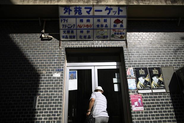 Comerciante fecha a porta de sua tabacaria no complexo de apartamentos de Kasumigaoka. Jinno será despejado de sua casa pela segunda vez pelo mesmo motivo (Foto: Issei Kato/Reuters)