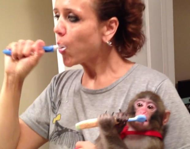Yasmin escova os dentes, acompanhada de seu macaco, que mantinha em casa ilegalmente (Foto: Reprodução)