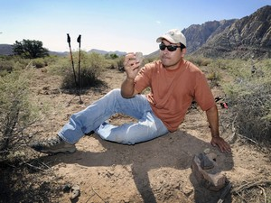 Paleontólogo Josh Bonde, da Universidade de Nevada, analisa fóssil encontrado em parque estadual. (Foto: AP Photo/Las Vegas Review-Journal, David Becker)