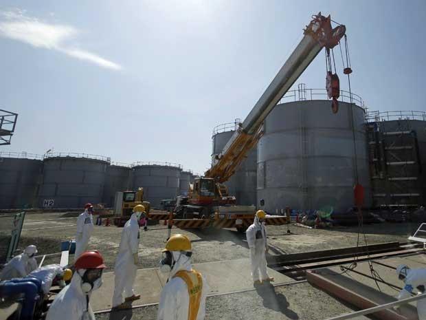 Funcionário mede radioatividade ao redor de tanque de água em usina de Fukushima. (Foto: Tepco/AFP Photo)