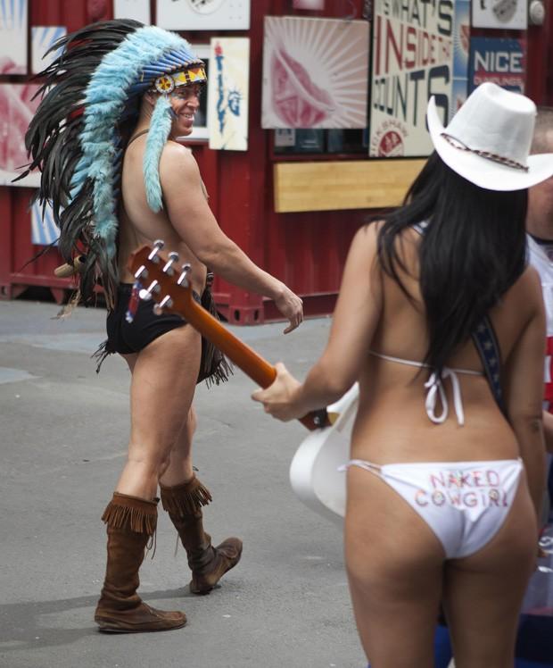 """Um homem vestido de """"Índio Pelado"""" sorri para mulher vestida de """"Cowgirl nua"""" na Times Square, em Nova York (EUA) (Foto: Carlo Allegri/Reuters)"""