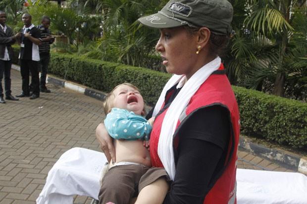 Membro da Cruz Vermelha carrega criança após ataque em shopping (Foto: Khalil Senosi/AP)