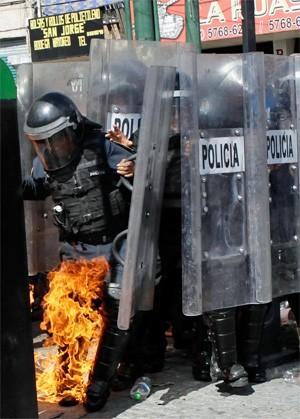 Fogo de coquetel molotov atinge policial em protesto na capital mexicana (Foto: Reuters)