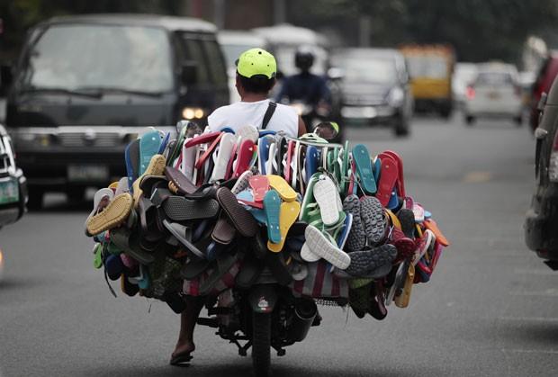 Um vendedor transformou sua moto em uma loja ambulante pelas ruas de Manila, nas Filipinas. Ele foi fotografado nesta segunda-feira (2) andando com uma moto superlotada de chinelos na capital filipina (Foto: Aaron Favila/AP)