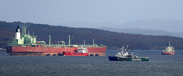 Navio do Greenpeace 'Arctic Sunrise' é escoltado por um barco da guarda costeira russa em Kola Bay, na base naval de Severomorsk, na Península de Kola, no extremo norte da Rússia, nesta terça (24) (Foto: Efrem Lukatsky/AP)