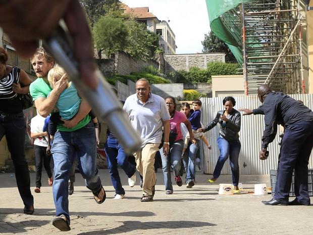 Um policial aponta uma arma para dar cobertura a clientes que correm de tiroteio no shopping Westgate em Nairóbi neste sábado (21) (Foto: Noor Khamis/Reuters)