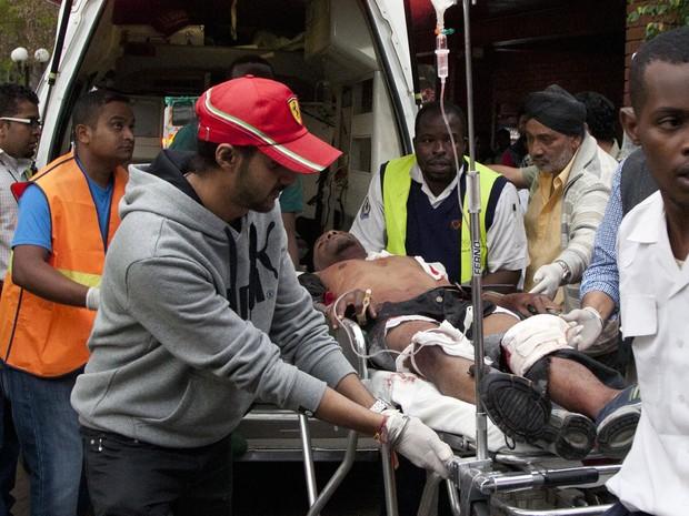 Homem ferido é atendido por âmbulância após tiroteio em shopping em Nairóbi (Foto: Jason Straziuso/AP)
