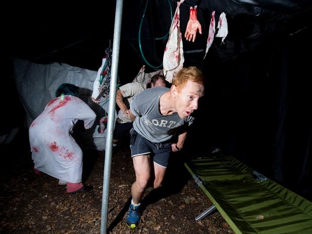 Participante de corrida foge de 'zumbi' neste sábado (5), no Reino Unido (Foto: AFP PHOTO/Leon Neal)