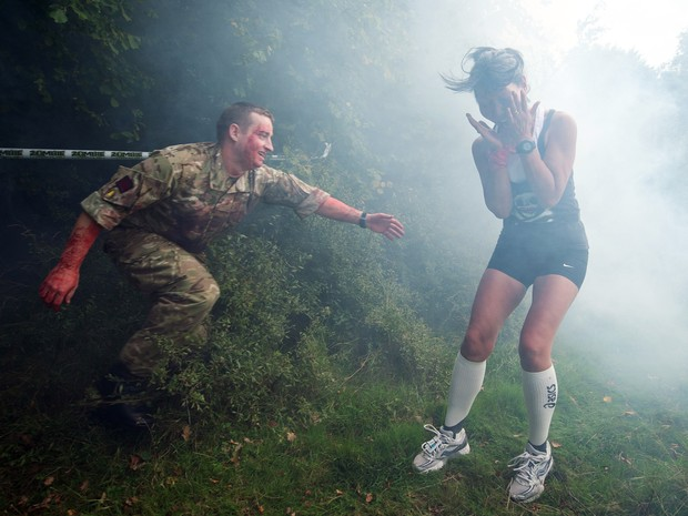 "Homem vestido de ""zumbi"" tenta ""infectar"" participante de corrida no Reino Unido (Foto: LEON NEAL / AFP)"