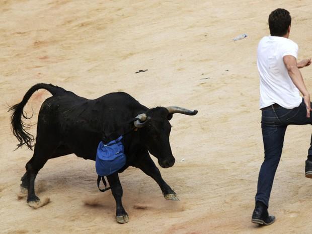 12 de julho - Touro 'roubou' a mochila de um corredor. A bolsa ficou presa em seu chifre enquando o rapaz tentava fugir do animal (Foto: Joseba Etxaburu/Reuters)