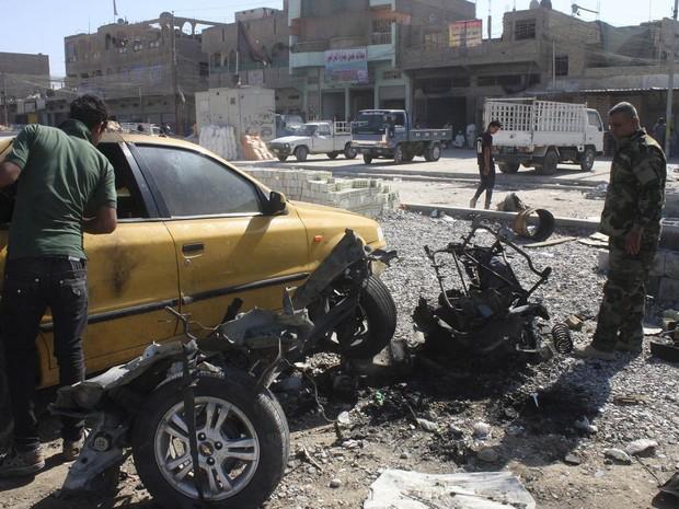 Policial checa os destroços de um carro-bomba usado em um atentado em Bagdá, no Iraque. Ao menos 37 pessoas morreram e mais de 120 ficaram feridas nesta segunda-feira em uma série de atentados com carros-bomba na cidade e seus arredores. (Foto: Qahtan al-Sudani/Reuters)
