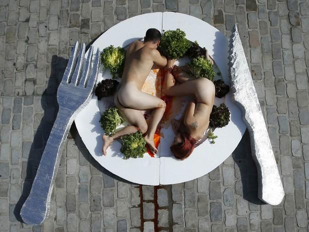 Casal 'se serve' nu em um prato gigante em protesto promovendo o vegetarianismo no centro de Barcelona, na Espanha. (Foto: Albert Gea/Reuters)