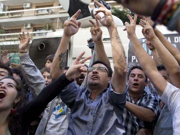 Simpatizantes da presidente argentina Cristina Kirchner comemoram o sucesso da cirurgia em frente a clínica em Buenos Aires nesta terça-feira (8) (Foto: Natacha Pisarenko/AP)