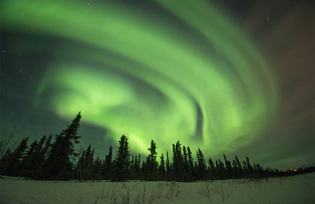 A aurora boreal é resultado da interação de partículas de vento solar com a atmosfera da Terra (Foto: Havre Daily News/Lindsay Brown/AP)