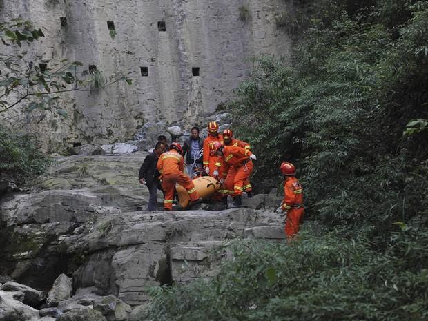 Equipe de resgate carrega o corpo de Victor Kovats, encontrado no parque chinês um dia após o salto de paraquedas (Foto: AP)