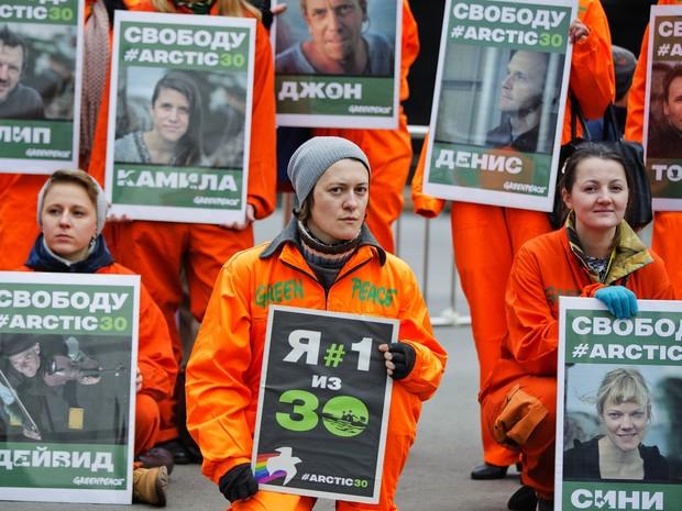 Imagem divulgada pelo Greenpeace, feita nesta terça-feira (24), mostra Ana Paula (em destaque) com outros membros da tripulação a bordo do navio 'Arctic Sunrise' enquanto são rebocados pela guarda costeira russa (Foto: Greenpeace/AP)