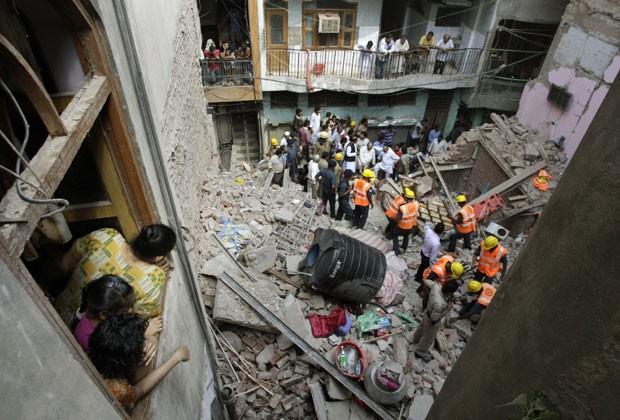 Mulher olha para destroços de prédio que desabou na Índia (Foto: Tsering Topgyal/AP)