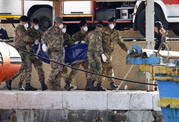 Imagem feita neste domingo mostra policiais segurando corpo de vítima do naufrágio ocorrido na última quinta-feira. (Foto: Antonio Parrinello/Reuters)