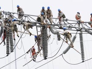 Trabalhadores realizam trabalho de manutenção em uma subestação de energia elétrica em Xuzhou, na China (Foto: China Daily/Reuters)