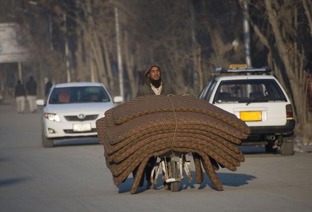 Homem carrega pilha de colchões em carrinho de mão no Afeganistão (Foto: Johannes Eisele/AFP)