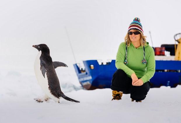 Foto mostra Barbara Tucker, passageira do navio preso entre o gelo na Antártica, ao lado de pinguim neste domingo (29) (Foto: Andrew Peacock /www.footloosefotography.com/AFP)