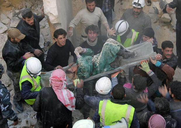 Corpo de mulher é retirado de escombros de prédio após bombardeio (Foto: AFP)
