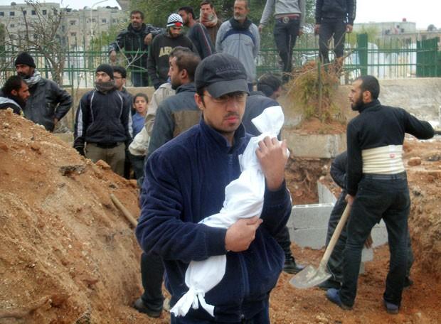 Homem segura corpo de filho de 1 ano que teria morrido de fome no campo de refugiados palestinos de Yarmuk, ao sul de Damasco, durante uma cerimônia funerária nesta segunda-feira (27) (Foto: STR/AFP)