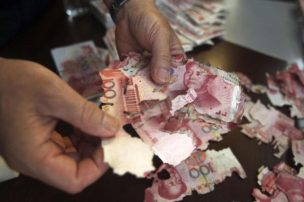 Chinesa tentou trocar cerca de 400 mil iuans após cédulas serem comidas por formigas (Foto: Stringer/Reuters)