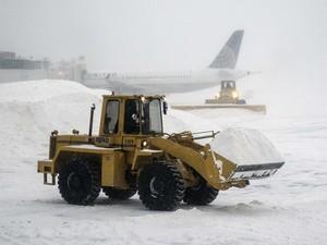 Máquinas pesadas limpam a neve acumulada no aeroporto de LaGuardia, durante uma tempestade de inverno em Nova York (Foto: Zoran Milich/Reuters)