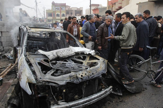 Iraquianos olham cena de ataque de carro-bomba em Kirkuk neste domingo (6); quatro pessoas morreram e outras 14 ficaram feridas (Foto: Ako Rasheed/Reuters)